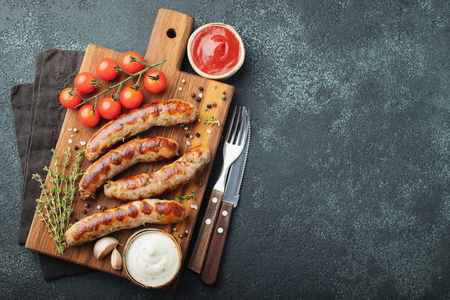 Fried sausages with sauces and herbs on a wooden serving Board. Great beer snack on a dark background. Top view with copy space.
