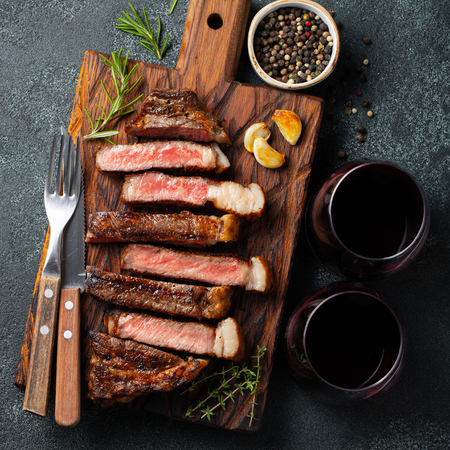 Sliced steak Striploin, grilled with pepper, garlic, salt and thyme served on a wooden chopping Board with a glass of red wine on a dark stone background. Top view.