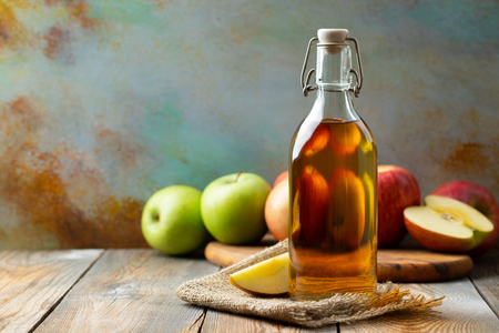 Apple vinegar. Bottle of apple organic vinegar or cider on wooden background. Healthy organic food. With copy space. Banque d'images