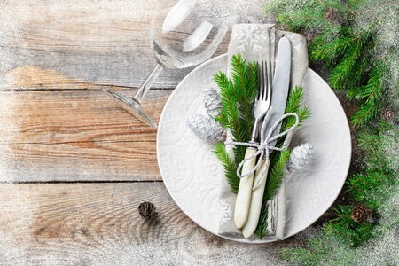 Christmas table setting with christmas decorations. White plate, Cutlery, fir cones and towel with snowflakes on old rustic wooden background. Frosty the snow frame. Top view, copy space. Flat lay.