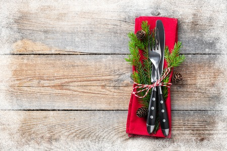 Christmas table setting with christmas decorations. Cutlery, fir cones and towel with snowflakes on old rustic wooden background. Frosty the snow frame. Top view, copy space. Flat lay.