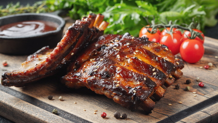 Closeup of pork ribs grilled with BBQ sauce and caramelized in honey. Tasty snack to beer on a wooden Board for filing on dark concrete background.