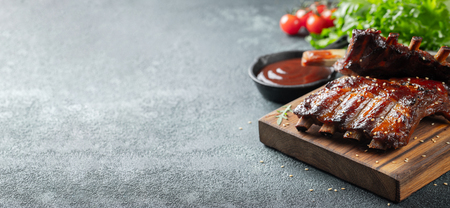 Closeup of pork ribs grilled with BBQ sauce and caramelized in honey. Tasty snack to beer on a wooden Board for filing on dark concrete background. With copy space.