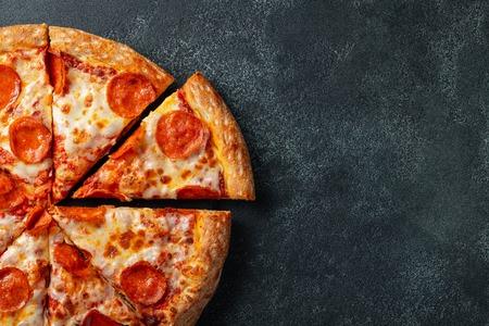 Leckere Peperoni-Pizza und Kochzutaten Tomaten Basilikum auf schwarzem Beton Hintergrund. Draufsicht der heißen Peperonipizza. Mit Kopienraum für Text. Flach legen