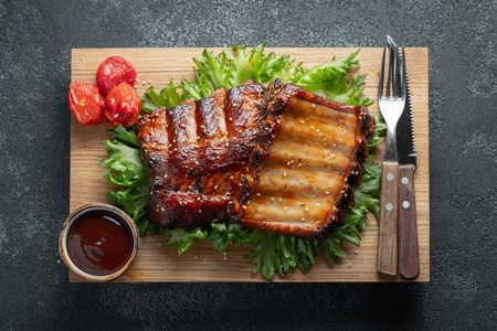 Closeup of pork ribs grilled with BBQ sauce and caramelized in honey on a bed of salad frisse. Tasty snack to beer on a wooden Board for filing on dark concrete background. Top view. Flat lay.