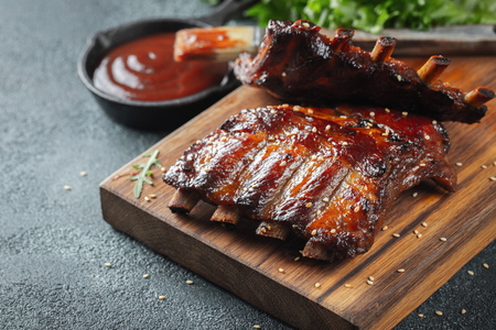 Closeup of grilled pork ribs with BBQ sauce and caramelized in honey  on a wooden board