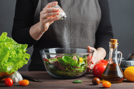 Woman chef in the kitchen preparing vegetable salad. Healthy Eating. Diet Concept. A Healthy Way Of Life. The girl sprinkles salt in a salad on a dark background. Banque d'images