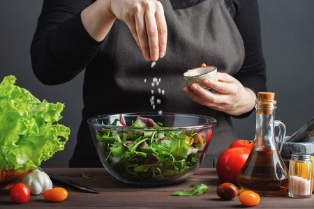 Woman chef in the kitchen preparing vegetable salad. Healthy Eating. Diet Concept. A Healthy Way Of Life. To Cook At Home. For Cooking. The girl sprinkles salt in a salad on a dark background Banque d'images