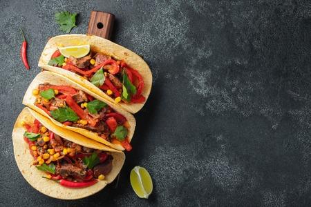 Mexikanische Tacos mit Rindfleisch, Gemüse und Salsa. Tacos al Pastor auf Holzbrett auf schwarzem Hintergrund. Draufsicht mit Kopienraum