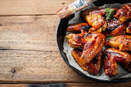 Alitas de pollo al horno en salsa barbacoa en una sartén de hierro fundido sobre una vieja mesa rústica de madera. Foto de archivo