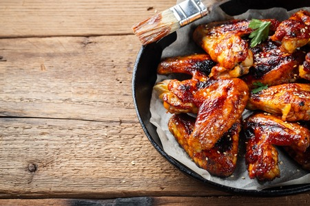 Baked chicken wings in barbecue sauce in a cast iron pan on an old wooden rustic table. Stock fotó