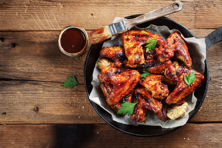 Baked chicken wings in barbecue sauce in a cast iron pan on an old wooden rustic table. Top view with copy space.
