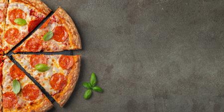 Sabrosa pizza de pepperoni con albahaca sobre fondo de hormigón marrón. Vista superior de la pizza de pepperoni caliente. Con espacio para copiar texto. Endecha plana. Foto de archivo