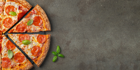 Tasty pepperoni pizza with basil on brown concrete background. Top view of hot pepperoni pizza. With copy space for text. Flat lay.