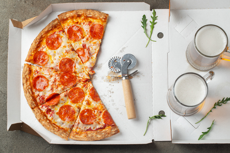 Italian fast food. Delicious hot pepperoni pizza in a box, and glass of beer sliced and served on brown table, close up view. Concept of fast food and unhealthy diet. Top view. Flat lay.