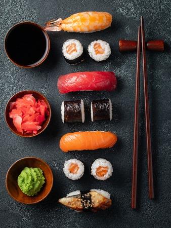 Set of sushi and maki on dark stone table. Top view. Flat lay.