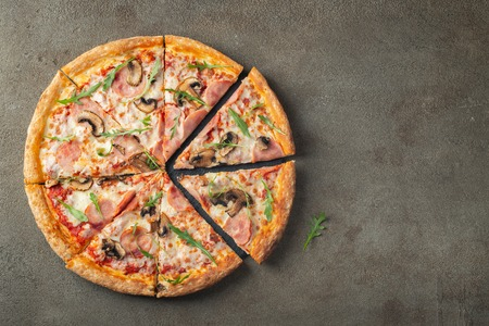 Italian fast food. Delicious hot pizza with ham and champignons sliced and served on brown concrete table, close up view. Menu photo. Top view with copy space. Flat lay.