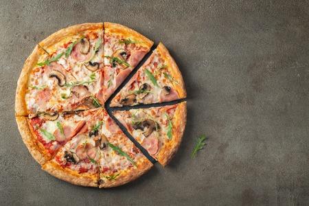 Italienisches Fastfood. Köstliche heiße Pizza mit Schinken und Champignons in Scheiben geschnitten und auf braunem Betontisch serviert, Nahaufnahme. Menü Foto. Draufsicht mit Kopienraum. Flach liegen.