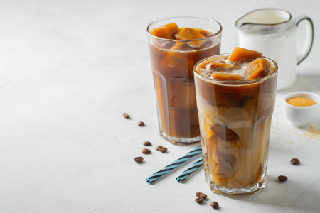 Ice coffee in a tall glass with cream poured over and coffee beans. Cold summer drink on a light background. With copy space.