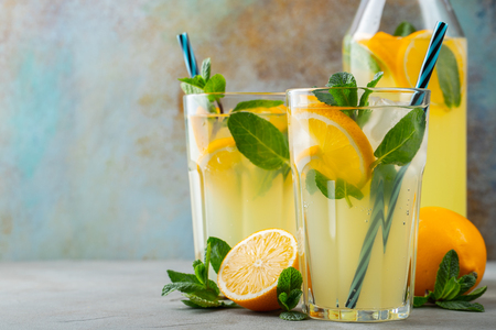 Two glass with lemonade or mojito cocktail with lemon and mint, cold refreshing drink or beverage with ice on rustic blue background. Copy space.
