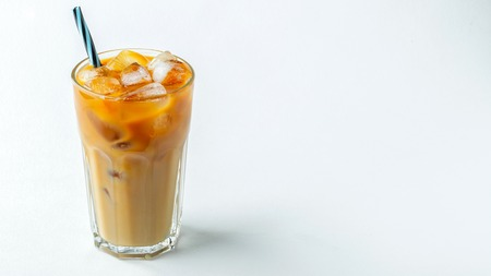 Ice coffee in a tall glass with cream poured over and coffee beans. Cold summer drink on a white background. With copy space.