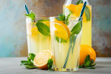 Dos vasos con limonada o cóctel mojito con limón y menta, bebida refrescante fría o bebida con hielo sobre fondo azul rústico.