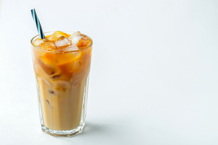 Ice coffee in a tall glass with cream poured over and coffee beans. Cold summer drink on a light background. With copy space