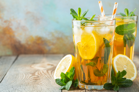 Traditional iced tea with lemon and ice in tall glasses on a wooden rustic table. With copy space.