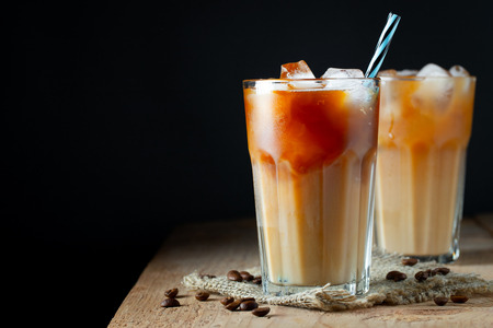 Ice coffee in a tall glass with cream poured over, ice cubes and beans on a old rustic wooden table. Cold summer drink with tubes on a black background with copy space