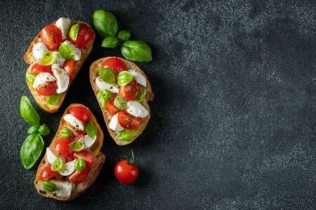 Bruschetta con pomodori, mozzarella e basilico su fondo scuro. Antipasto o spuntino italiano tradizionale, antipasto. Vista dall'alto con spazio di copia. Lay piatto Archivio Fotografico