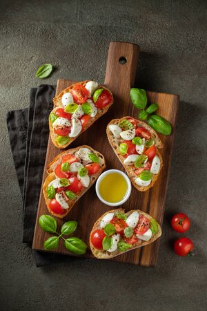 Bruschetta with tomatoes, mozzarella cheese and basil on a cutting board. Traditional italian appetizer or snack, antipasto. Top view. Flat lay.