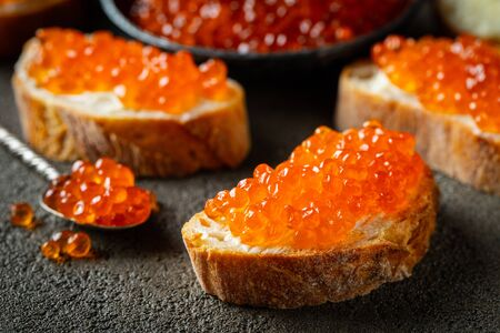 Delicious Sandwiches with red caviar on a dark concrete background.