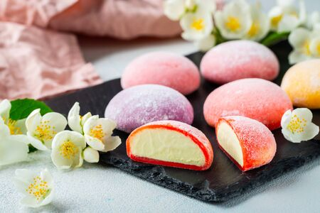 Multi-colored Japanese ice cream Mochi in rice dough and Jasmine flowers on a concrete blue background. Traditional Japanese dessert on a black slate.