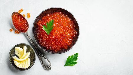 Delicious red caviar in black bowl on a light concrete background. Top view with copy space. Flat lay.