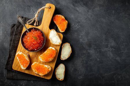 Close-up red caviar in bowl and Sandwiches on wooden cutting board on black background. Top view with copy space. Flat lay. 版權商用圖片
