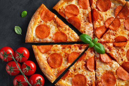 Tasty pepperoni pizza and cooking ingredients tomatoes basil on black concrete background. Top view of hot pepperoni pizza. Flat lay Imagens