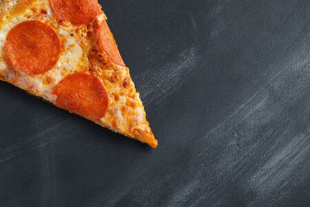 A slice of pepperoni pizza on a dark concrete background. Top view of hot pepperoni pizza. With copy space for text. Flat lay