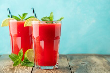Watermelon slushie with lime and mint, summer refreshing drink in tall glasses on a light blue background. Sweet cold smoothie with copy space Stock fotó
