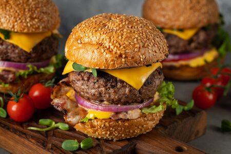 Eine Reihe hausgemachter köstlicher Burger aus Rindfleisch, Speck, Käse, Salat und Tomaten auf hellem Betonhintergrund. Fettes ungesundes Essen Nahaufnahme Standard-Bild