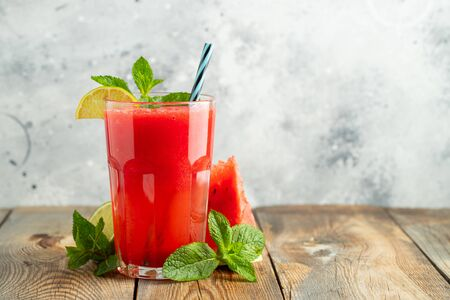 Watermelon slushie with lime and mint, summer refreshing drink in tall glasses on a light background. Sweet cold smoothie with copy space Stock fotó