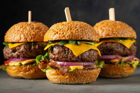 A set of homemade delicious burgers of beef, bacon, cheese, lettuce and tomatoes on a dark concrete background. Fat unhealthy food close-up