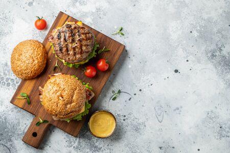 Leckerer gegrillter hausgemachter Burger mit Rindfleisch, Tomaten, Käse, Speck und Salat auf hellem Steinhintergrund mit Kopierraum. Ansicht von oben. Fast-Food- und Junk-Food-Konzept. Flach legen