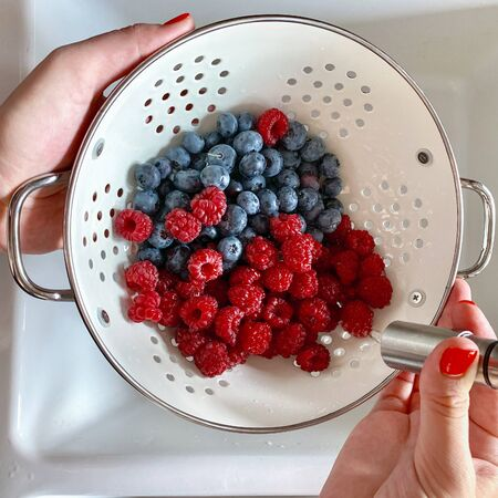 Woman hand washing raspberries and blueberries in a large metal bowl with water on the kitchen sink. Top view
