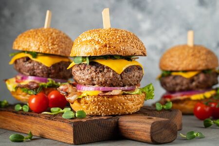 A set of homemade delicious burgers of beef, bacon, cheese, lettuce and tomatoes on a light concrete background. Fat unhealthy food close-up Stockfoto - 129156216