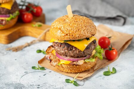 A set of homemade delicious burgers of beef, bacon, cheese, lettuce and tomatoes on a light concrete background. Fat unhealthy food close-up Stockfoto - 129156218