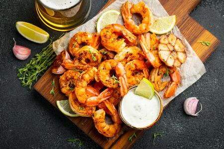 Grilled shrimps or prawns served with lime, garlic and white sauce on a dark concrete background. Seafood. Top view. Flat lay.