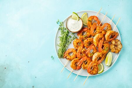 Grilled shrimp skewers or langoustines served with lime, garlic and sauce on a light blue concrete background. Seafood. Top view with copy space. Flat lay