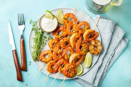Grilled shrimp skewers or langoustines served with lime, garlic and sauce on a light blue concrete background. Seafood and beer. Top view. Flat lay Stock fotó