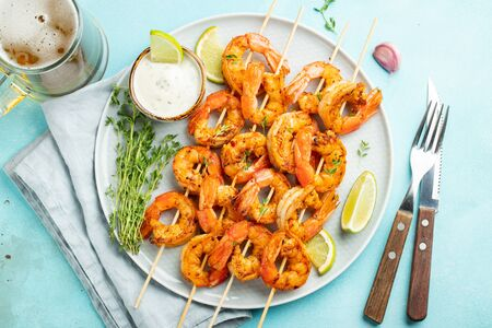 Grilled shrimp skewers or langoustines served with lime, garlic and sauce on a light blue concrete background. Seafood and beer. Top view. Flat lay. Stock fotó