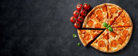 Tasty pepperoni pizza on black concrete background. Top view of hot pepperoni pizza. With copy space for text. Flat lay. Banner. 版權商用圖片